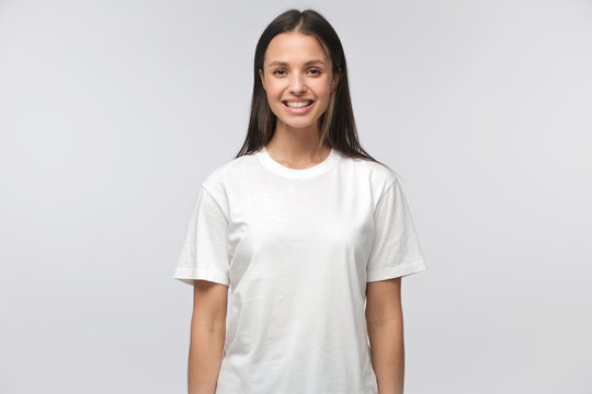 Portrait of smiling young woman in white t-shirt looking at camera, isolated on gray background