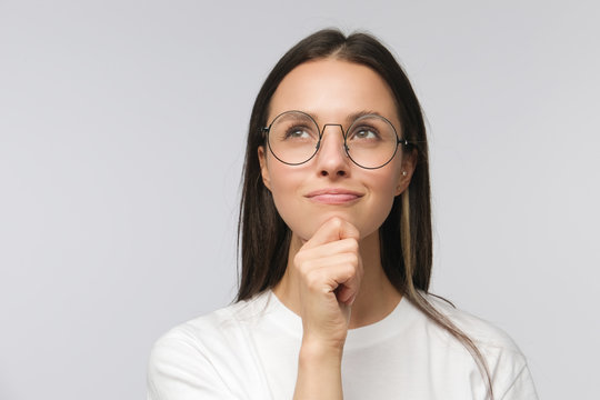 Portrait of young woman with dreamy cheerful expression, thinking, wearing eyeglasses, isolated on gray background