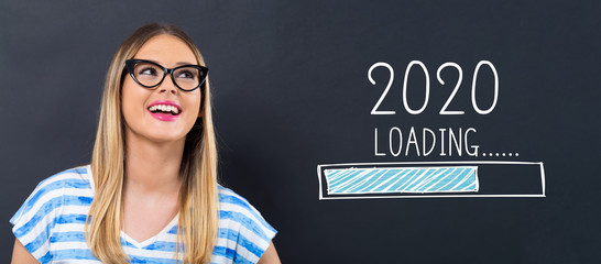 Loading new year 2020 with happy young woman in front of a blackboard