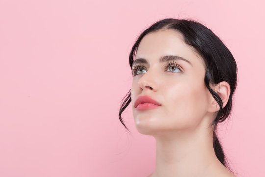 Beautiful young woman with skin care theme on a pink background