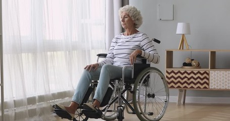 Fotomurales - Thoughtful sad old woman sit on wheelchair alone at home