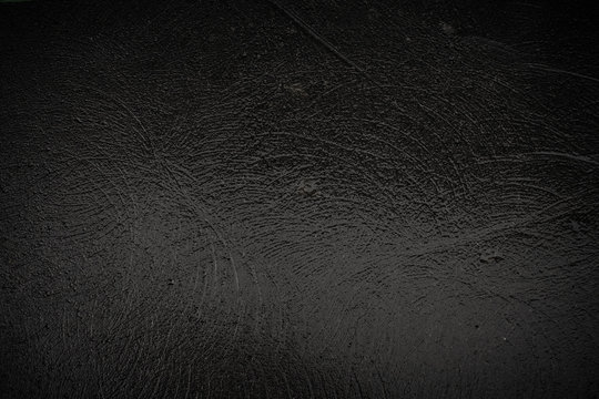 Texture of black granite wet stone with traces of grinding