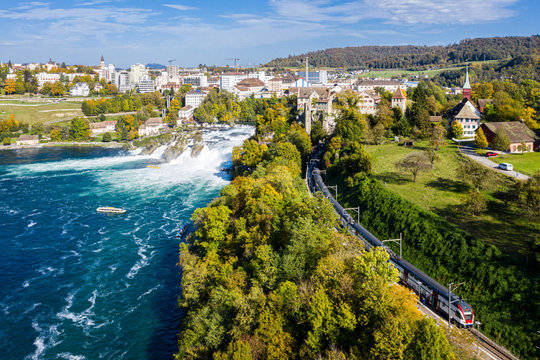 Panoramic aerial view of Rhine Falls and cityscape of Neuhausen am Rheinfall town, Switzerland. Red Swiss train, and tourist boats in waterfall. Cliff-top Schloss Laufen castle, Laufen-Uhwiese
