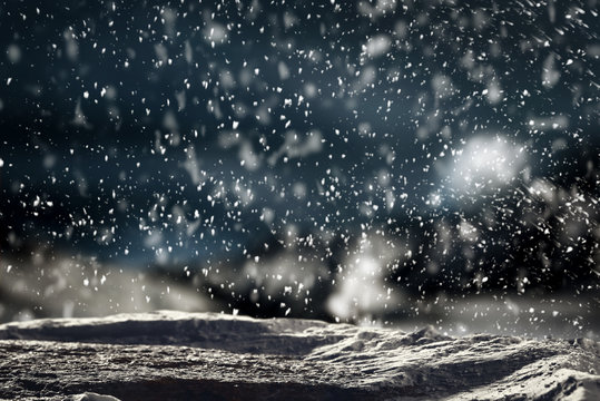 Christmas background with space for advertising products and decorations. Snowy glimmering and shiny winter landscape with falling snowflakes and snow surface.