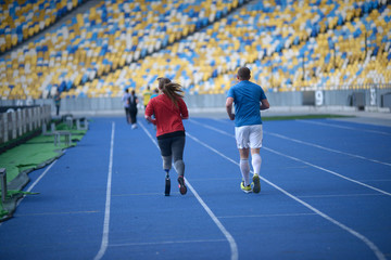 Man and young disabled woman with the prosthetic leg running on the track of the stadium, evening light