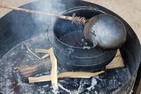 Black pot in which wax is melted to produce candles