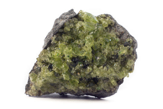 Rock with peridot olivine mineral from the USA isolated on a pure white background.