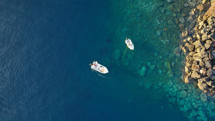 Aerial top down photo of fishing boat in small port of Ammoudi, Santorini island, Cyclades, Greece