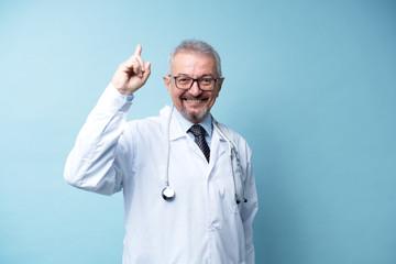 White doctor smiling man pointing finger up