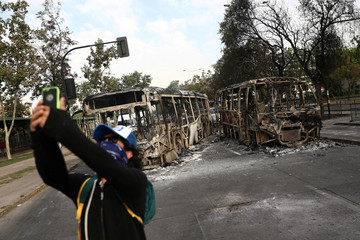 Masked man takes a picture near burned busses after a protest in Santiago