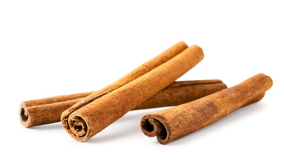 Three cinnamon sticks on a white background, isolated.