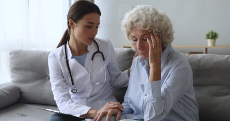 Fototapete - Young woman nurse doctor supporting comforting depressed old grandma patient