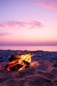 Fire on beach with pink sunset