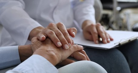 Fototapete - Woman doctor nurse holding hand of elderly grandma patient, closeup
