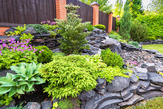 Landscape design of home garden. Beautiful stone landscaping in backyard in summer.