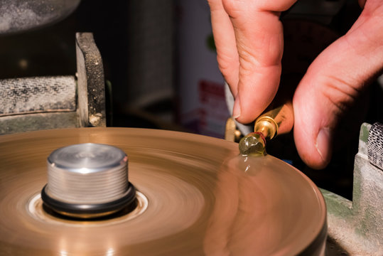 Craftsman cutting and polishing a green gemstone on a turning metal lap.