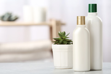 Wall Mural - Bottles with hair care cosmetics and succulent on table in bathroom, space for text