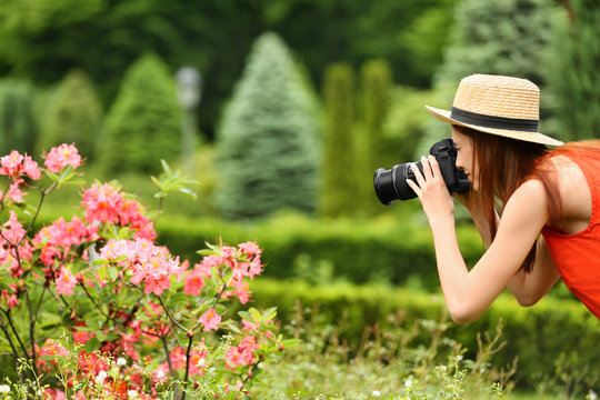 Photographer taking photo of blossoming bush with professional camera in park