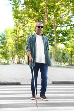 Mature blind person with white cane crossing street in city