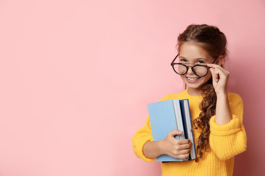 Cute little girl with glasses and books on pink background, space for text. Reading concept
