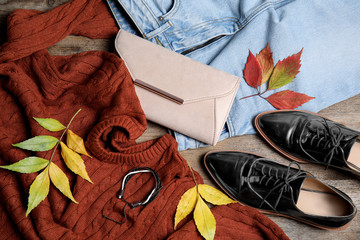 Fototapete - Flat lay composition with warm clothes and autumn leaves on wooden background