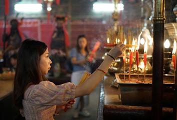 A woman burns incenses as she prays at Man Mo Temple in Hong Kong