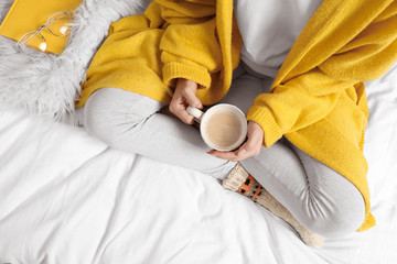 Fototapete - Woman with coffee wearing knitted socks on white fabric, top view. Warm clothes