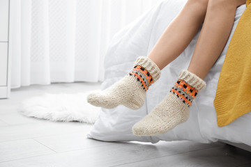 Fototapete - Woman wearing knitted socks on bed indoors, closeup. Warm clothes