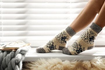 Fototapete - Woman wearing knitted socks on window sill indoors, closeup. Warm clothes
