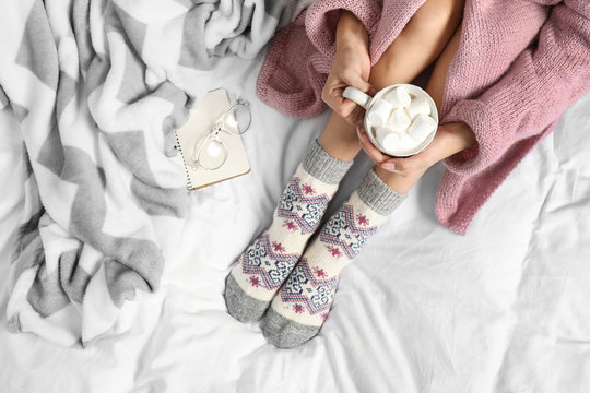 Woman with cocoa wearing knitted socks on white fabric, top view. warm clothes