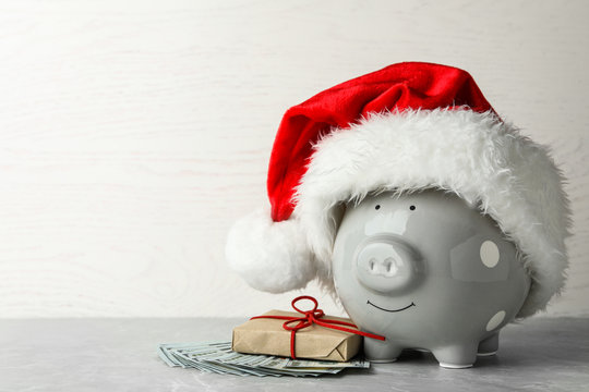 Piggy bank with Santa hat, gift box and dollar banknotes on grey table. Space for text