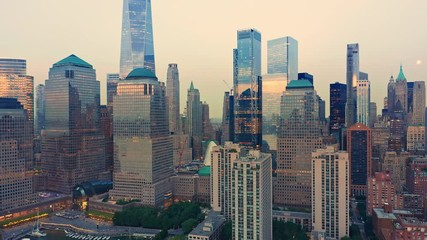 Fototapete - Drone footage with slow pull back away from New York City Lower Manhattan skyscrapers at dusk