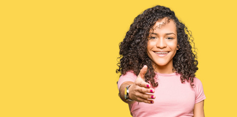 Young beautiful woman with curly hair wearing pink t-shirt smiling friendly offering handshake as greeting and welcoming. Successful business.