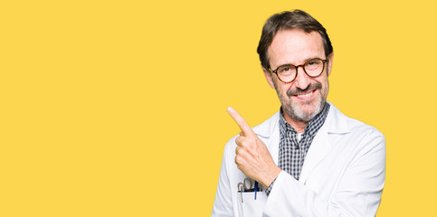 Middle age doctor men wearing medical coat cheerful with a smile of face pointing with hand and finger up to the side with happy and natural expression on face