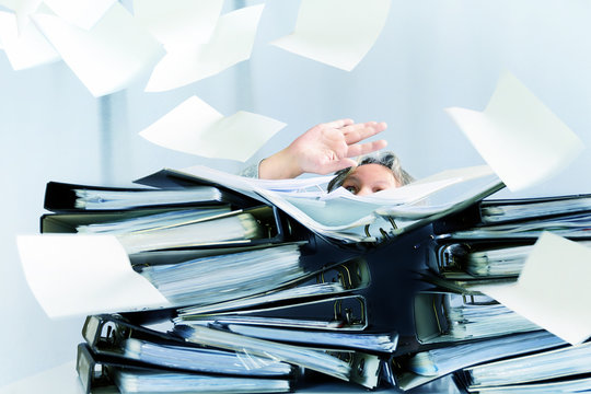 desperate woman behind high stacks of ring binders and lots of papers are flying around in the office, concept of excessive demands and increasing work in business