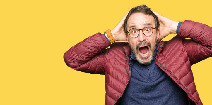 Middle age handsome man wearing glasses and winter coat Crazy and scared with hands on head, afraid and surprised of shock with open mouth