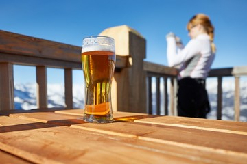 Glass of beer in the snowy mountains, woman taking pictures of the scenic landscape view