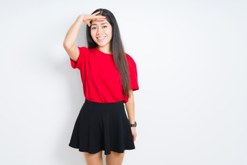 Beautiful brunette woman wearing red t-shirt and skirt over isolated background very happy and smiling looking far away with hand over head. Searching concept.