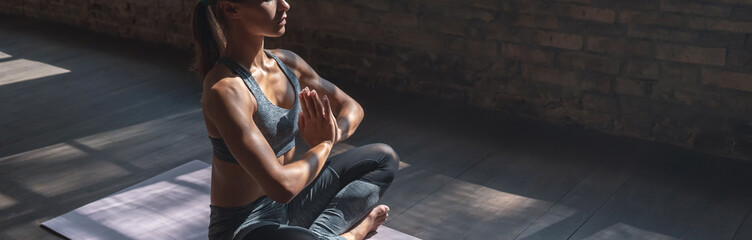 Calm fit sporty healthy mindful woman sit in lotus pose doing yoga exercise breathing fresh air meditating in gym lit with sunlight, stress free concept, horizontal banner website design, copy space