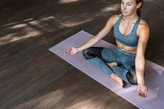 Mindful fit sporty healthy calm young woman sitting in lotus pose on mat doing yoga exercise breathing fresh air meditating in gym on wooden floor feel balance and no stress free concept, copy space