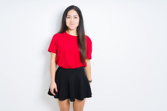 Beautiful brunette woman wearing red t-shirt and skirt over isolated background puffing cheeks with funny face. Mouth inflated with air, crazy expression.