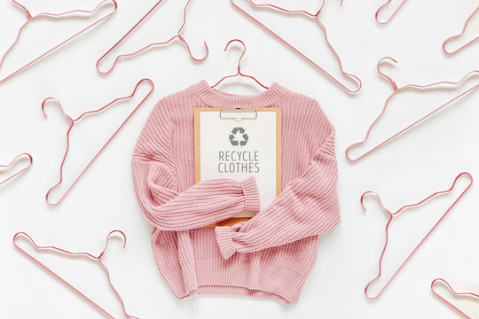 Recycle clothes concept. Pale pink knitted sweater with clipboard  on white background. Autumn and winter clothes.