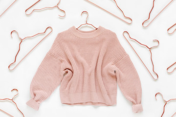 Pale pink knitted sweater with metallic hangers on white background. Autumn and winter clothes. Store, sale, fashion concept.
