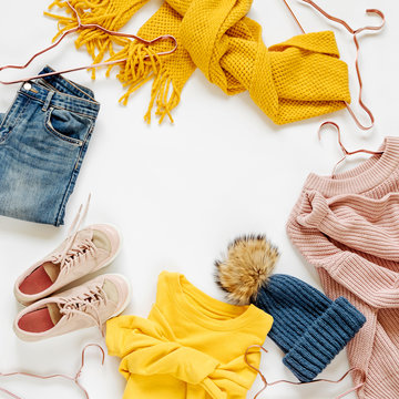 Warm sweaters, jeans, scarf, hat and other clothes. Women's autumn or winter outfit. Flat lay, top view.