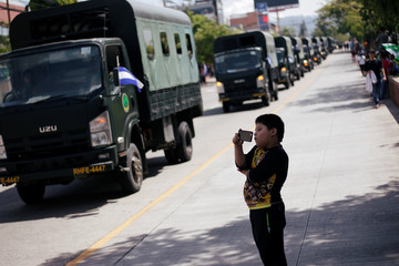 A child takes pictures of military trucks during a military parade to mark the 194th anniversary of the Honduras Army, in Tegucigalpa