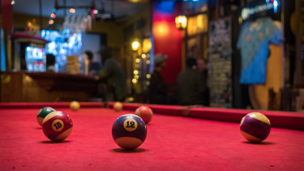 Pool table with several scattered balls. You can see ball 12 and 15. In the background you see people having drinks in what looks like a bar