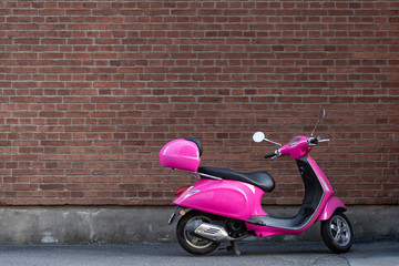 Pink Scooter in front of a brick wall