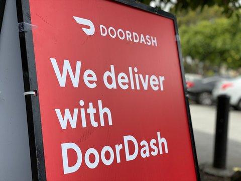 "DoorDash Food Delivery Sign in Parking Lot: ""We deliver with DoorDash"""