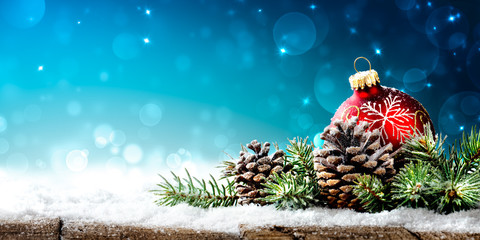 Christmas - Red Ornament, Pinecones And Branches On Snowy Wooden Table With Blue Bokeh Background