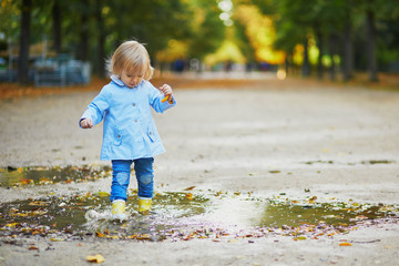 Child wearing yellow rain boots and jumping in puddle